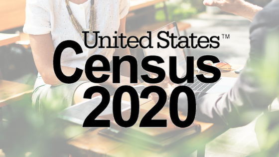 United States Census 2020 logo overlaid on a picture of two individuals sitting at a table and talking with plants in the foreground.