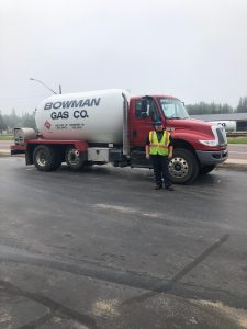 Justin Tuttle standing in front of his Bowman Gas, Co. propane truck in a paved parking lot.
