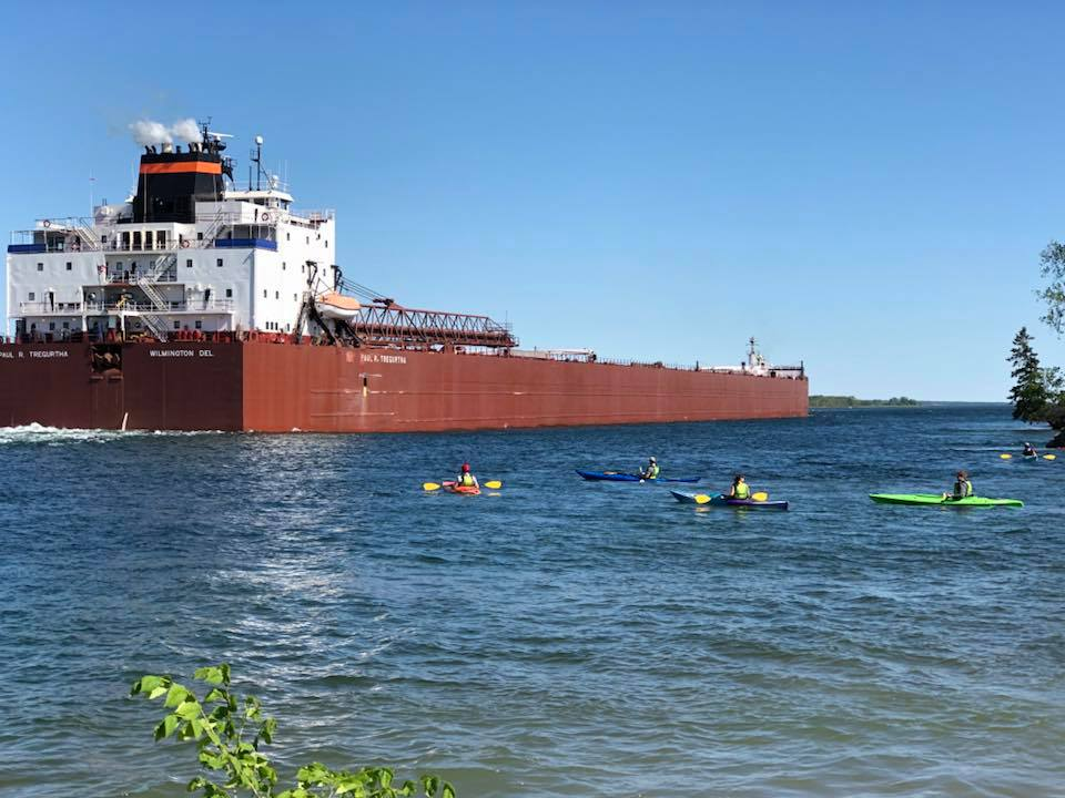 Five kayakers paddling next to a large brown and white freighter in the St. Marys River.