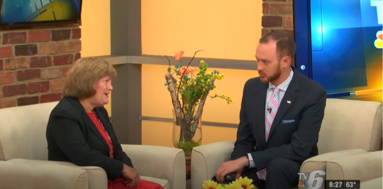 Denise sitting across from a man being interviewed on TV6 about the GoingPro program.