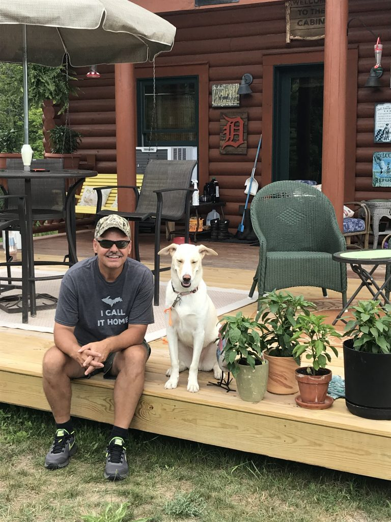 Jim Huff and his dog sitting on the porch of their home.
