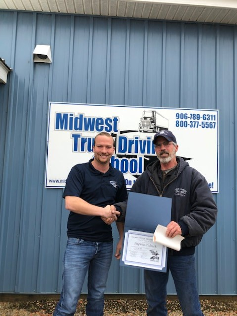 Stephen is standing in front of a Midwest Truck Driving School sign holding a certificate and shaking another man's hand.