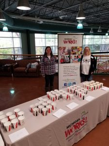 Two UPward Talent Council staff members are standing behind a table on which cups sit.