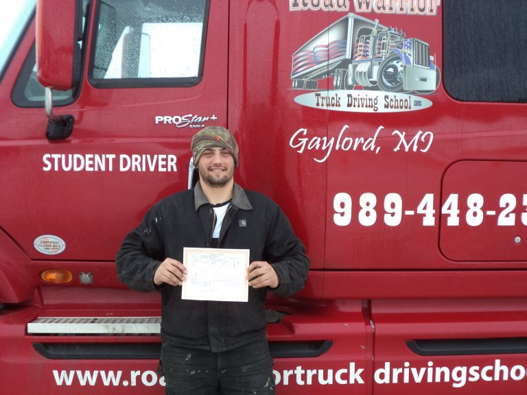 Joe standing in front of a red semi truck and holding a certificate of completion.