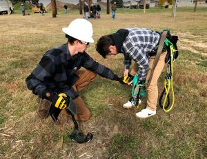 NMU Electrical Lineman student helps a JMG student put on a climbing harness on the ground.