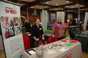 Beckie and Holly standing behind a table at the LSSU Career Fair with marketing merchandise on their table.