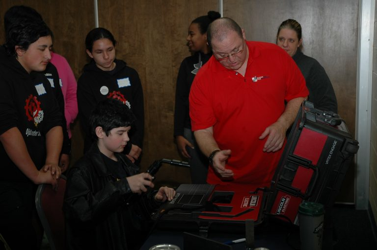 A student sits in front of a welding simulator with a welder in hand and a man in a red polo is standing next to him instructing him on how to weld.