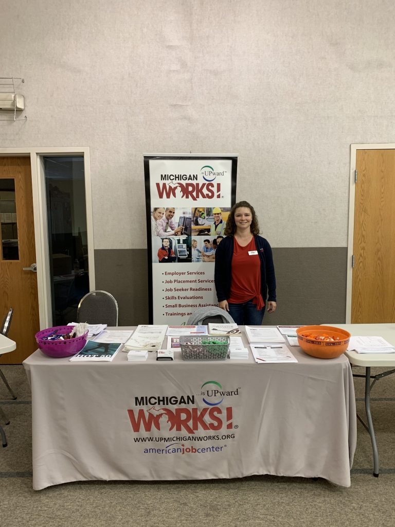 MI Works! staff member Amy standing behind a table with a MI Works! table cloth and stand-up sign.