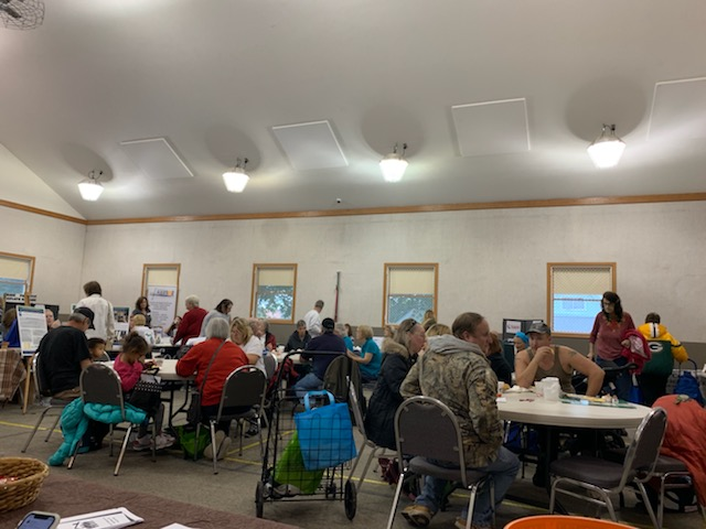Multiple tables set up inside the Schoolcraft County Resource Fair with many people sitting down at said tables.