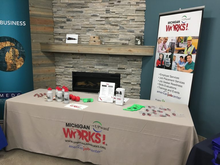 A Michigan Works! table set up with marketing items and handouts in front of a fireplace.