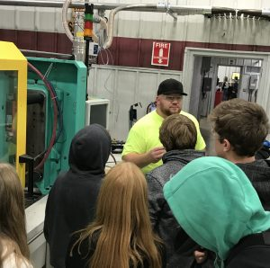 High school freshman stand with their backs turned to the camera as a man in a black hat and neon green t shirt explains a process to them in a manufacturing setting.