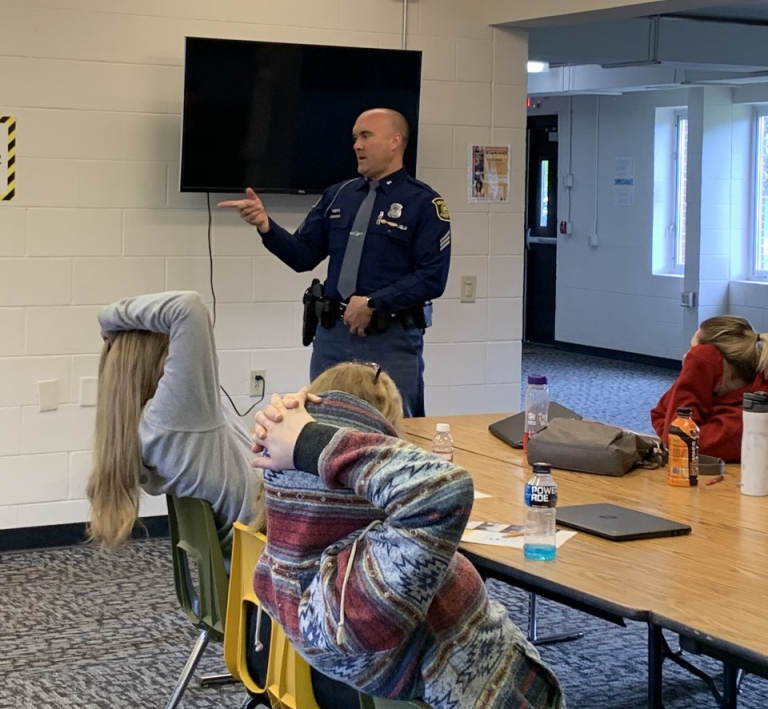 Sgt. Giannunzio stands in front of two kids who have their hands resting behind their heads as he speaks to a classroom of students.