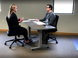 A man and a woman sit at a table during a mock interview. The man sits with his hands on the table and the woman is speaking using her hands for emphasis.