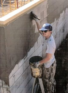 A young man on a ladder holding a bucket in his left hand and applying materials to cinder blocks with a paint brush with his left hand.
