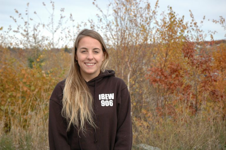 Erin stands in front of plants during the fall outside wearing a black hoodie with IBEW 906 written on it.