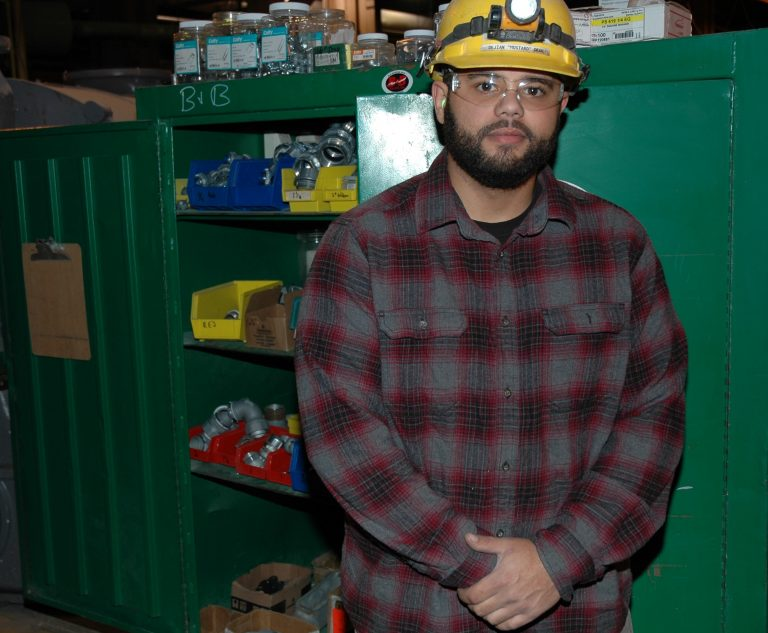 DeJian stands with his hands held together in front of his stomach. He is standing in front of a green tool chest while wearing safety glasses and a hard hat.