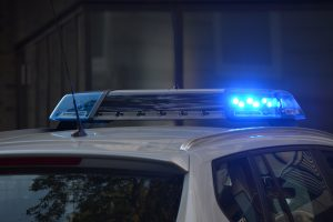 Stock photograph of the top of a police car with its blue lights on.