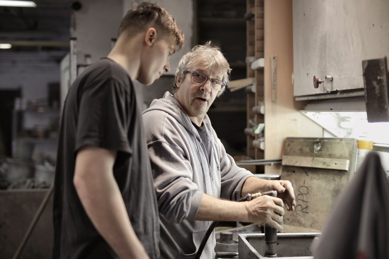 A man and a younger man work in an industrial setting.