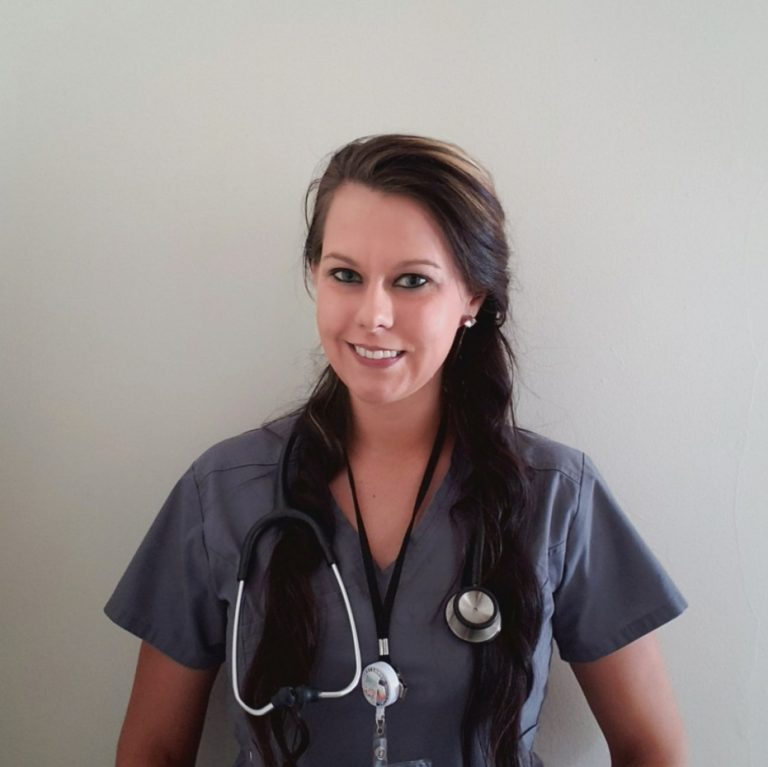 Nichole stands in front of a blank wall wearing gray scrubs, a stethoscope, and a badge.