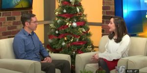 Tim sits across from Sarah with a Christmas tree between them during an interview.