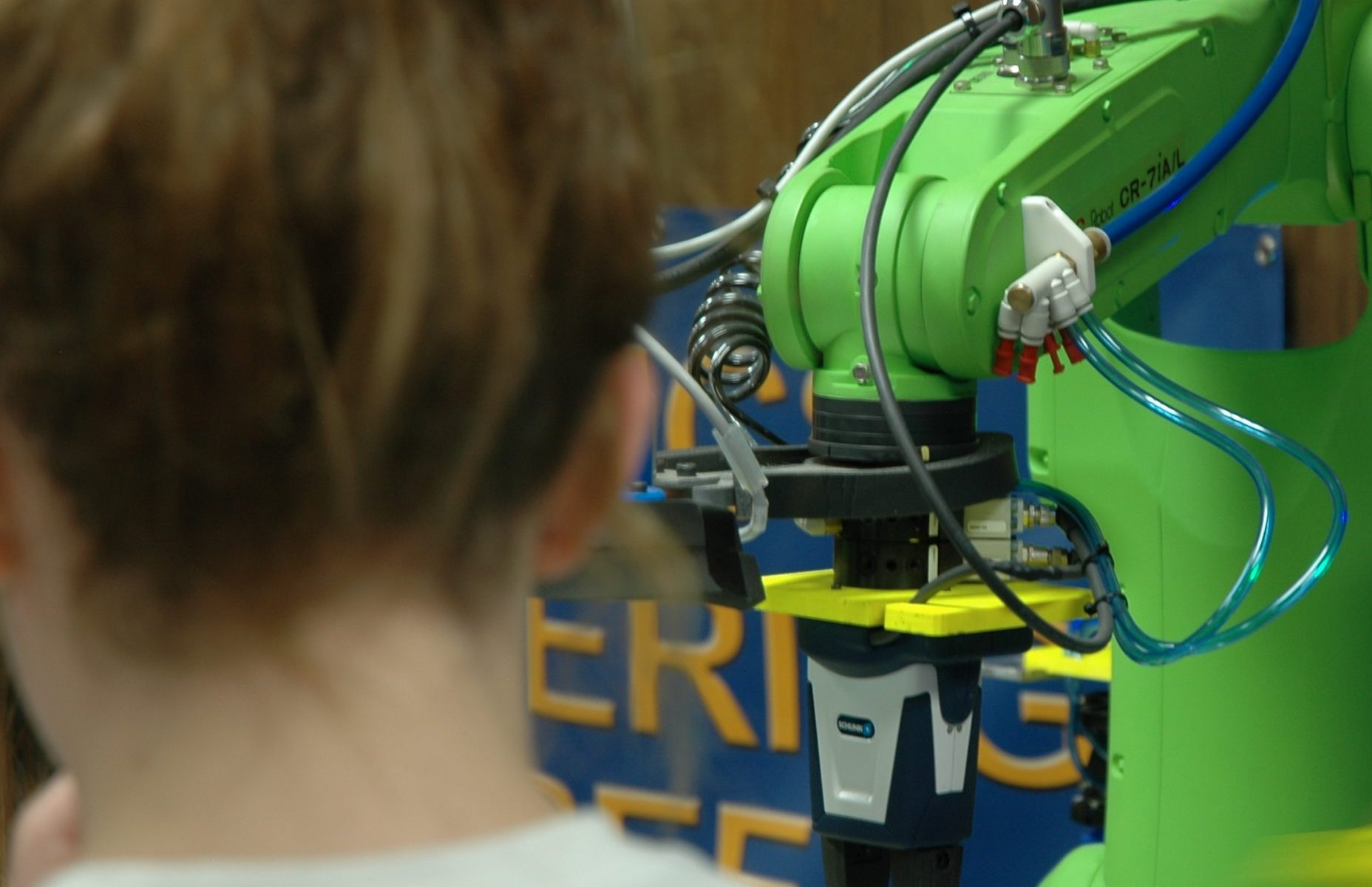 Image with a student in the foreground, and a green robotic arm in the background, which is in focus.