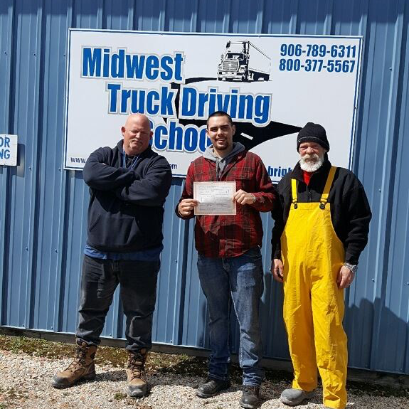 David stands in front of a Midwest Truck Driving School sign with a certificate in his hand, standing between two other men.