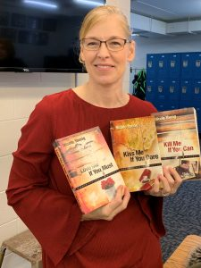 Nicole Young Potvin is posing for the camera in the classroom holding three of her books.