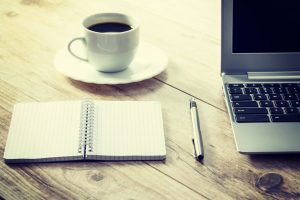 Stock image of a notebook with a pen sitting next to a cup of coffee and the left edge of a laptop on a wooden desk.