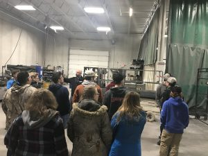 Students gather around a presenter at a Somero manufacturing center in the Upper Peninsula. Students stand with their backs to the camera as a man speaks in front of them.
