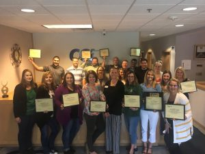 Members of CCI Systems stand in front of a reception desk posing for a picture and holding gold certificates.