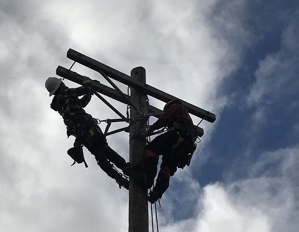 Two linemen work at the top of an electrical pole with a blue sky in the background.