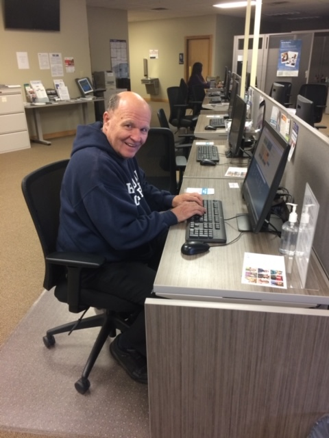 Samuel sits at a computer in an American Job Center and looks to the right to pose for a photograph.