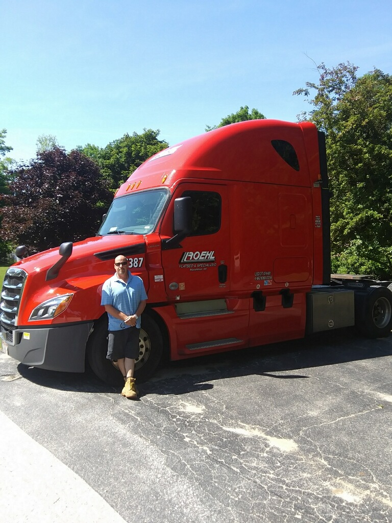A man in a blue shirt and shorts stands in front of a red semi truck.