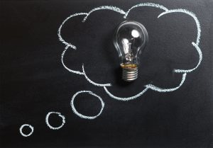 A light bulb sitting on a black chalk board outlined in a white thought cloud.