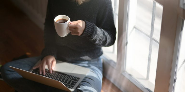 A woman sits cross legged with a laptop on her lap and coffee in her right hand.