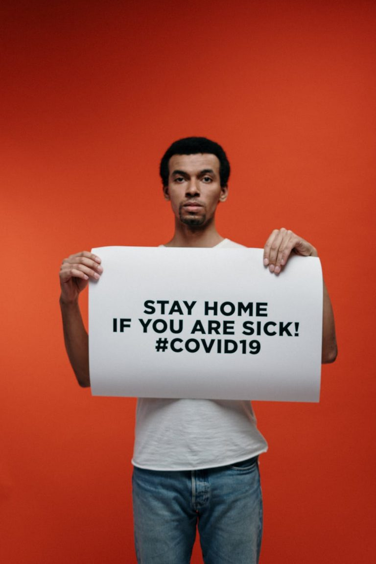 A man holding up a white sign that says, Stay home if you are sick! #COVID19