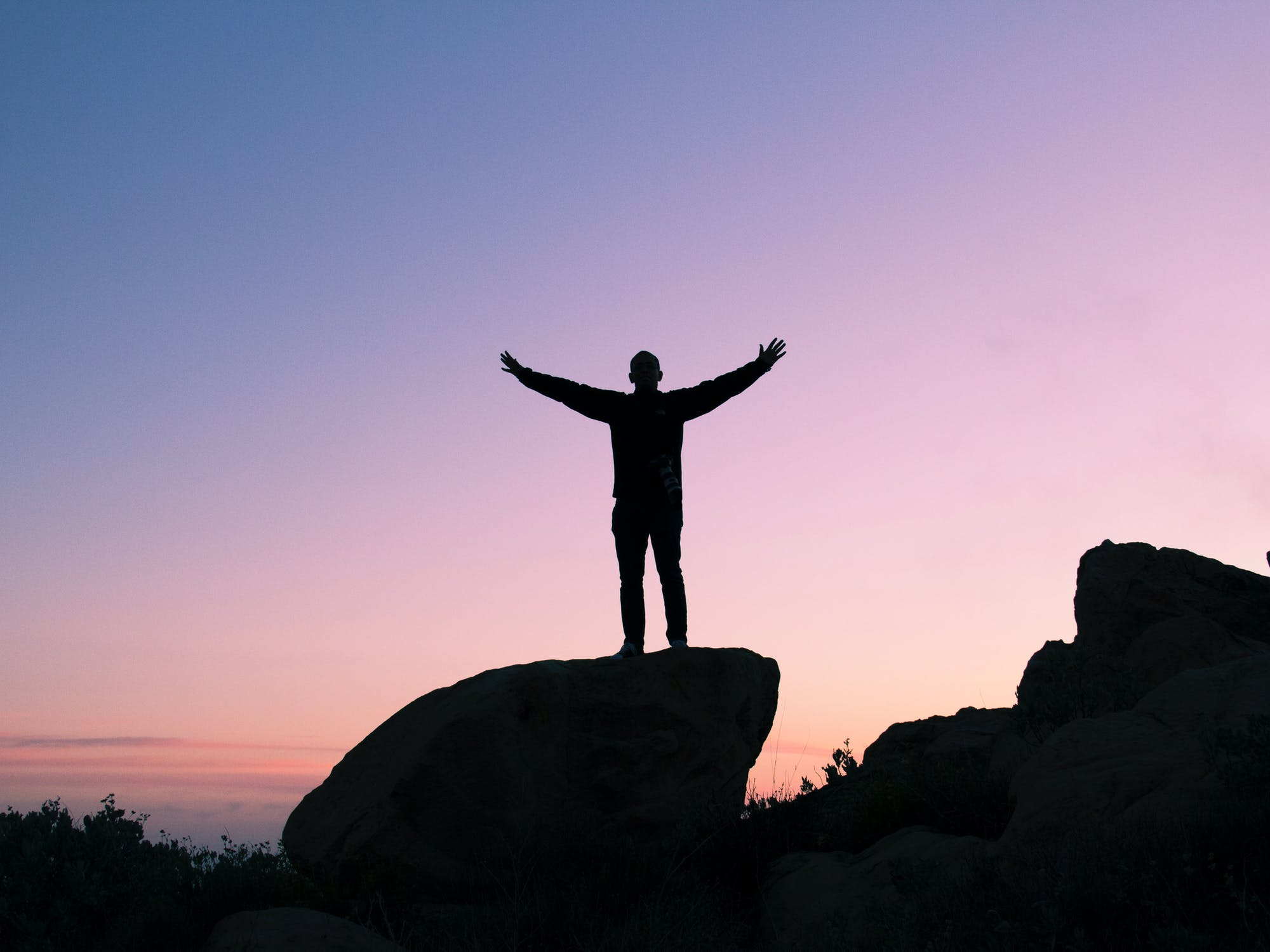 A silhouette of a person standing on a rock with their arms outstretched.