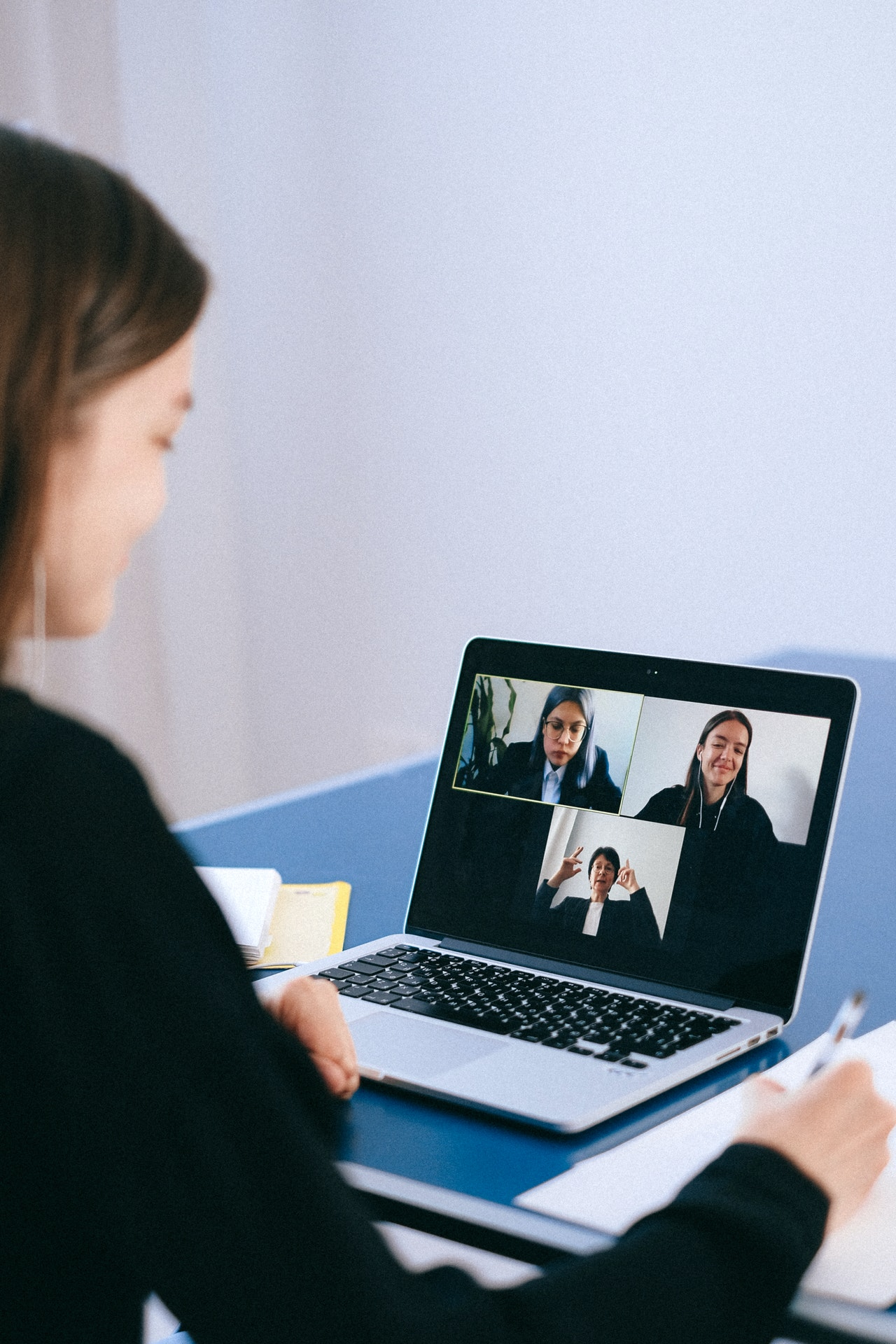 A woman communicates with other via video conferencing technology on a laptop.