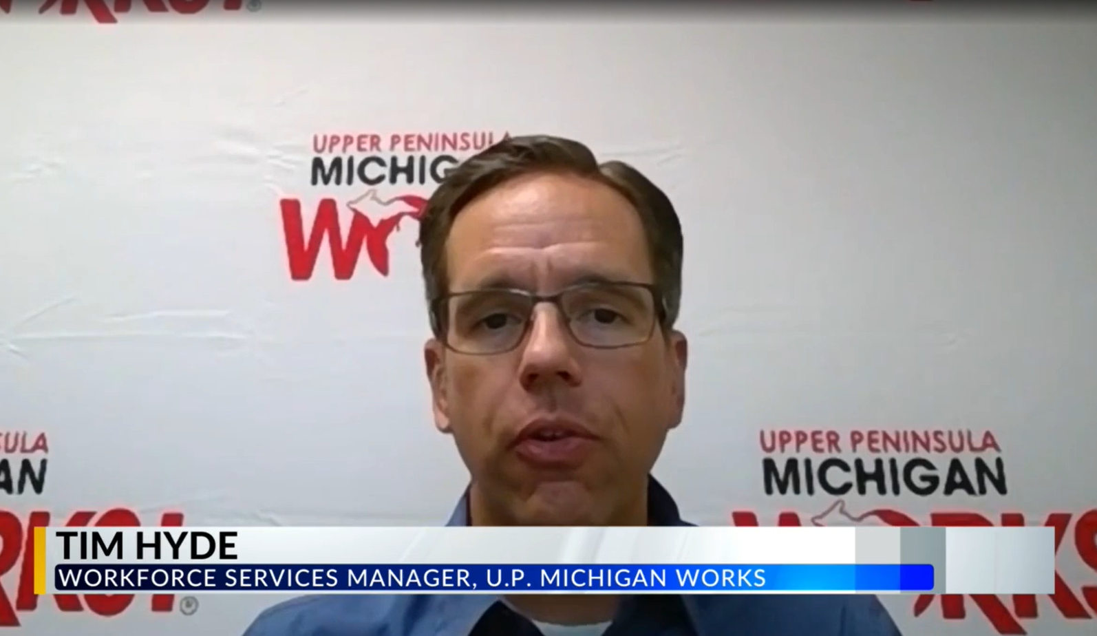 Tim Hyde sits in front of a white Michigan Works background during an interview.