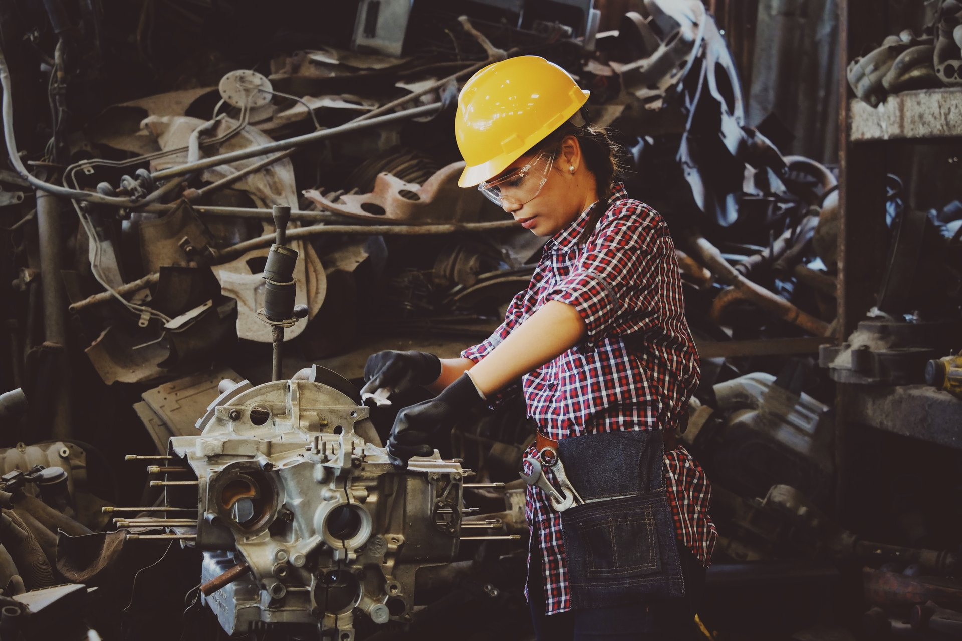A woman wearing safety equipment works on a piece of machinery in a factory setting.