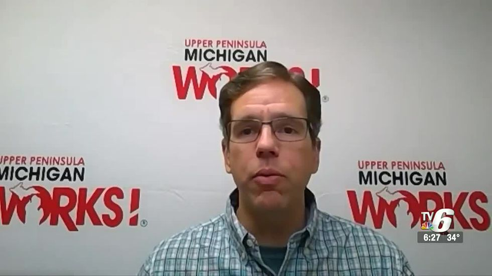 Tim Hyde sits in front of a UPMW background while conducting an interview.