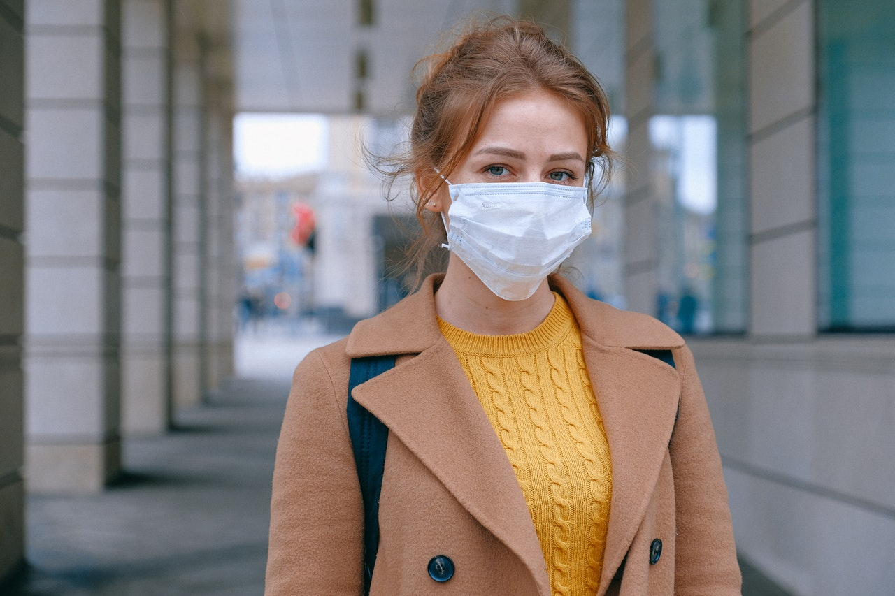 A woman outside in a brown jacket wears a mask.