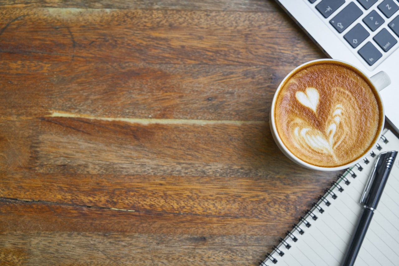 A cup of coffee sits on a wooden desk next to a laptop and a notebook.