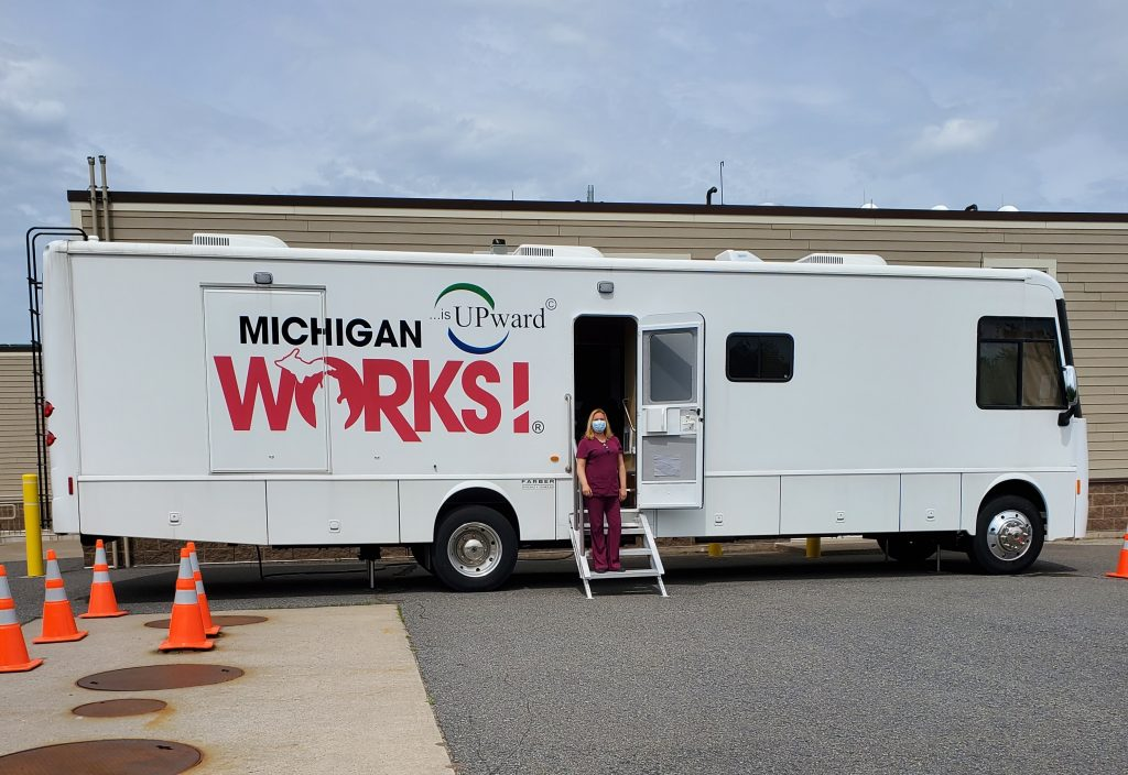 A woman stands in the doorway of our mobile unit in a parking lot.