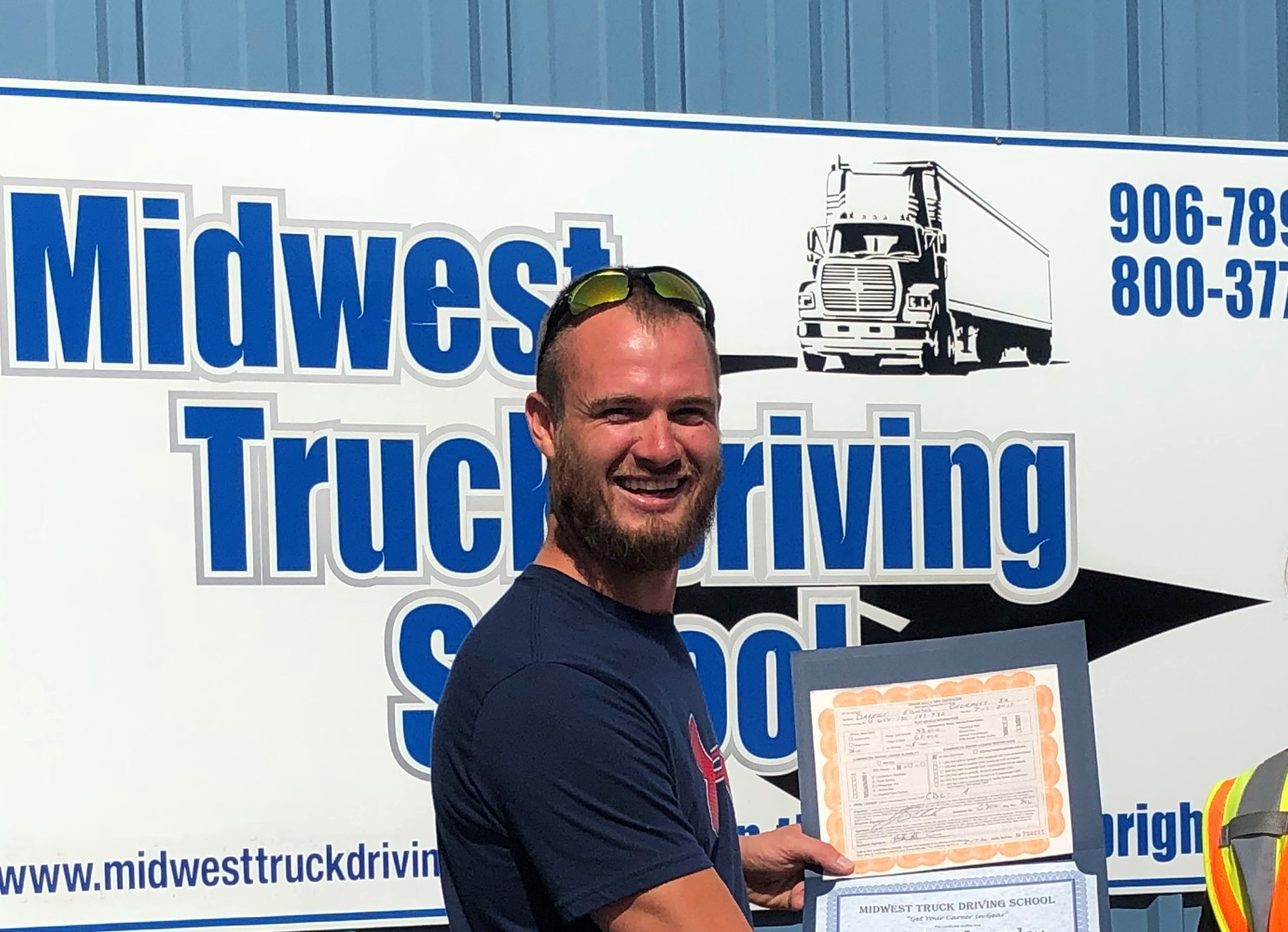 Darelle poses in front of a Midwest Truck Driving Sign with his certificate.