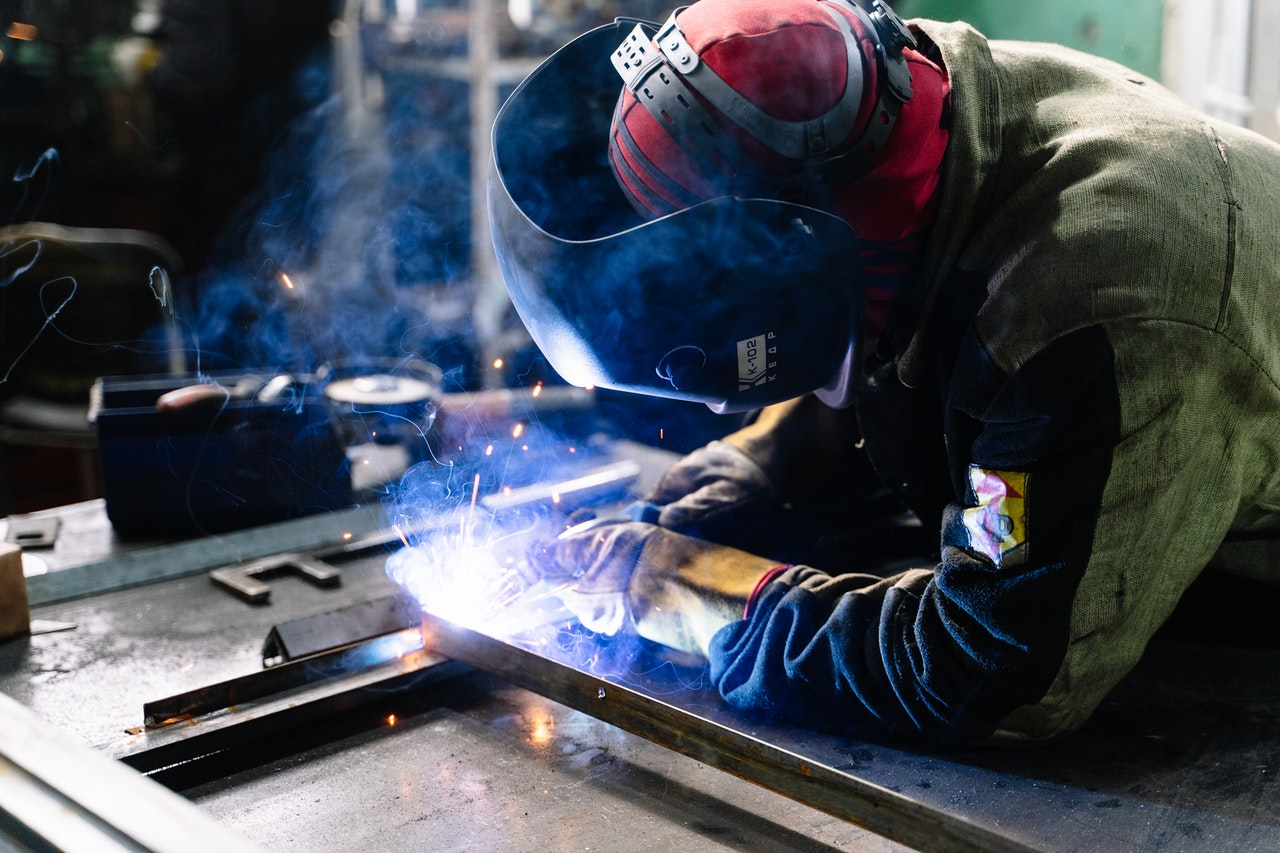 A person in welding gear uses a welding machine to weld metal.