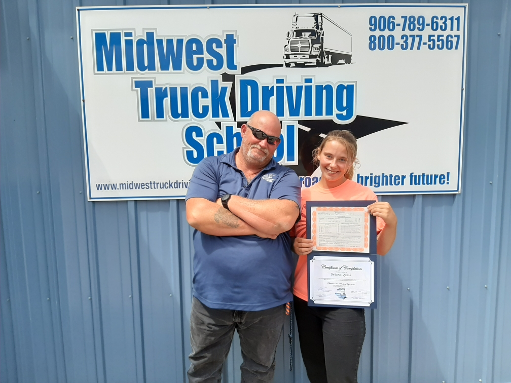 Briana stands with her instructor in front of a sign while holding her certificate.