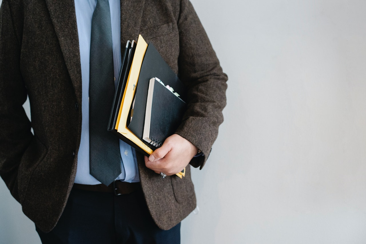A man in a blazer and tie holds folders and a notebook.