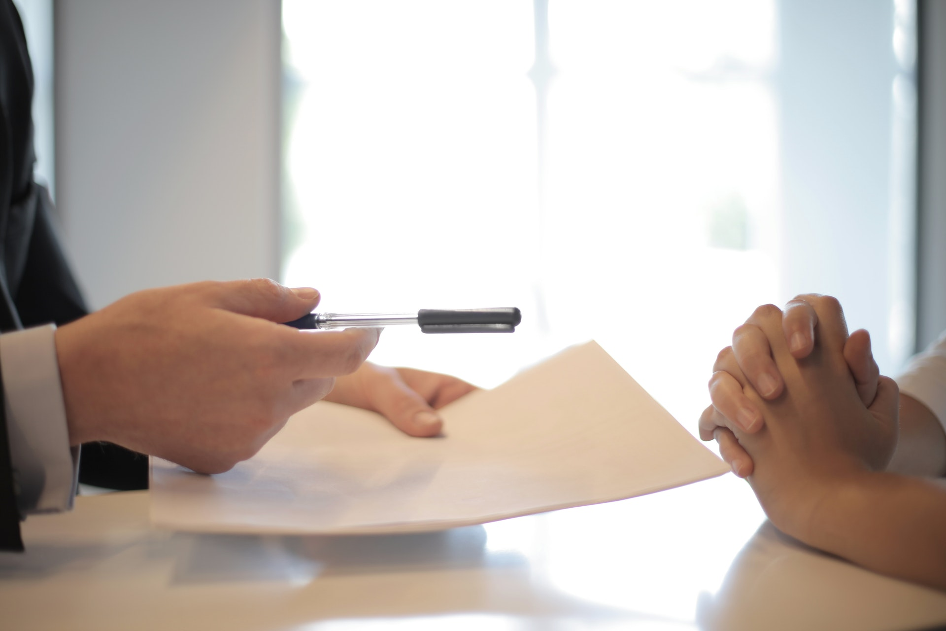 A person in business clothes holding a pen and paper sits across from someone with folded hands.
