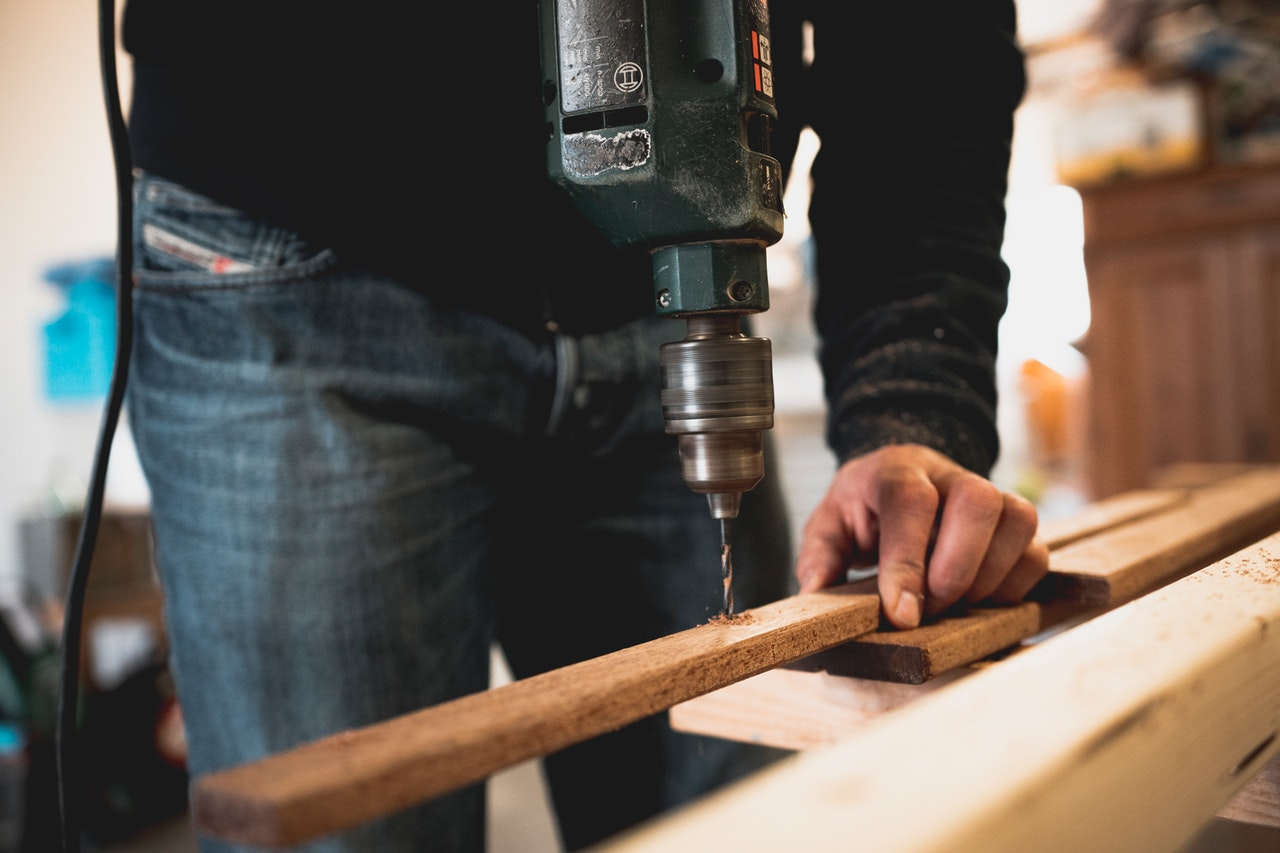 A person in a black shirt holds a piece of wood as they drill through it.